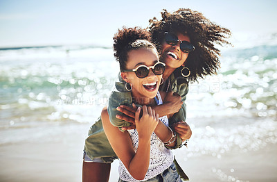 Buy stock photo Shot of two girlfriends enjoying themselves at the beach