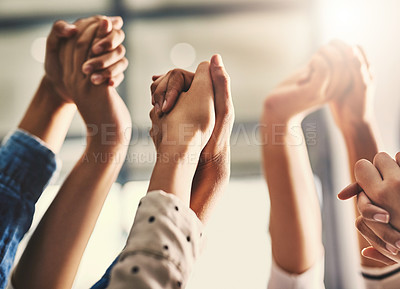 Buy stock photo Closeup shot of a group of unrecognizable people holding hands with their arms raised