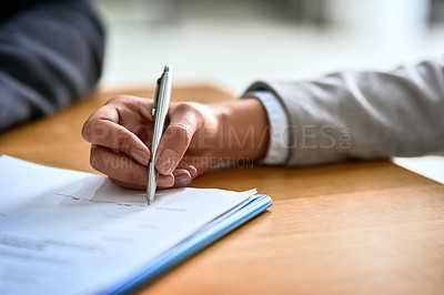Buy stock photo Cropped shot of a businessman and businesswoman completing paperwork together at a desk