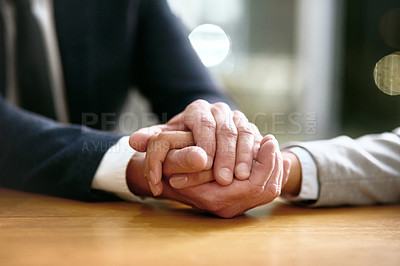 Buy stock photo Cropped shot of a businessman and businesswoman compassionately holding hands at a table