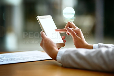 Buy stock photo Cropped shot of a businesswoman using a mobile phone at her desk in a modern office