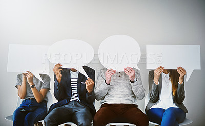 Buy stock photo Shot of a diverse group of businesspeople holding up speech bubbles while they wait in line