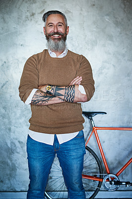 Buy stock photo Portrait of a middle aged man standing with his arms folded with a red bicycle in the back against a grey background