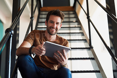 Buy stock photo Shot of a young designer working on his tablet while sitting on a staircase in the office