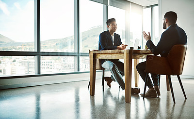 Buy stock photo Shot of two young businessmen having a discussion at a desk in a modern office