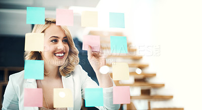 Buy stock photo Shot of a businesswoman arranging sticky notes on a glass wall in a modern office