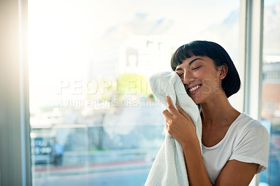 Buy stock photo Cropped shot of a young woman rubbing a freshly washed towel against her face