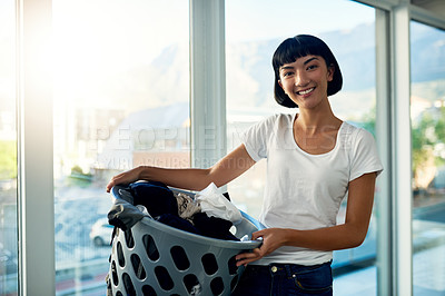 Buy stock photo Cropped shot of a young woman holding a laundry basket