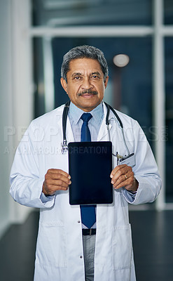 Buy stock photo Portrait of a mature doctor holding up a digital tablet with a blank screen in a hospital