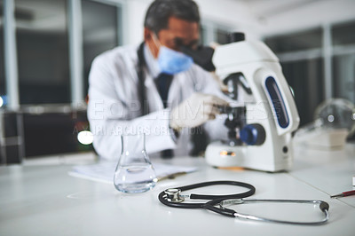 Buy stock photo Shot of a stethoscope on a laboratory table with a scientist using a microscope in the background