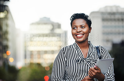 Buy stock photo Shot of a young businesswoman holding a digital tablet in the city