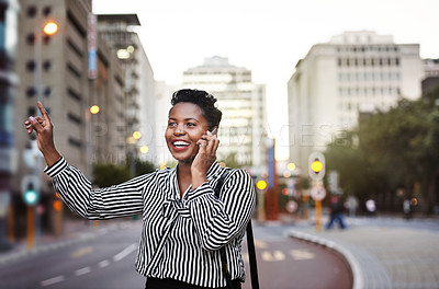 Buy stock photo Shot of a young businesswoman using a mobile phone while catching a cab in the city