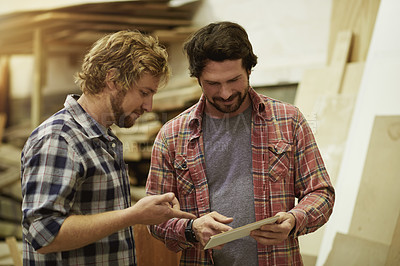 Buy stock photo Shot of two men working together on a digital tablet in their workshop
