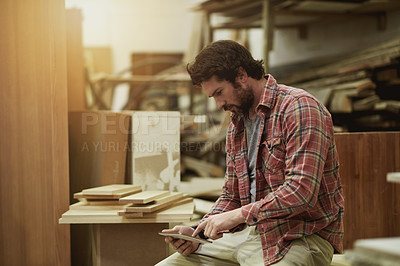 Buy stock photo Cropped shot of a man using his digital tablet in his workshop