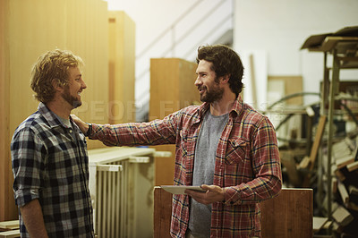 Buy stock photo Shot of two coworkers talking in a workshop