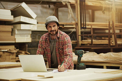 Buy stock photo Cropped shot of a man using his laptop in his workshop