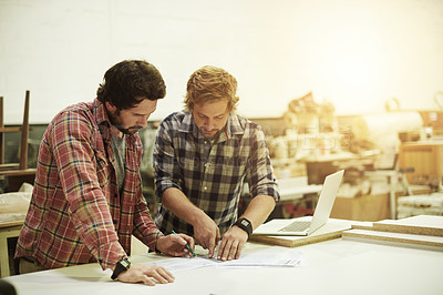 Buy stock photo Cropped shot of two craftsmen drawing up designs together