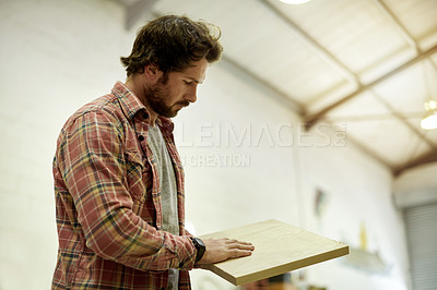 Buy stock photo Cropped shot of a man looking at a sample of wood in his workshop