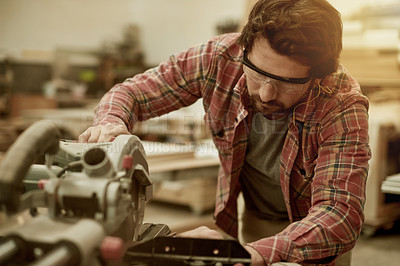 Buy stock photo Cropped shot of a carpenter cutting wood in his workshop