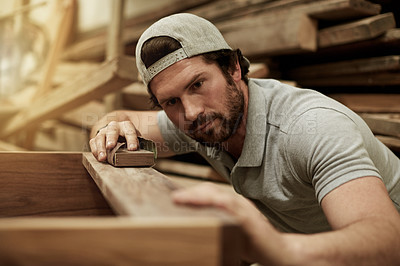 Buy stock photo Cropped shot of a handsome young carpenter sanding down one of his wood pieces in the workshop