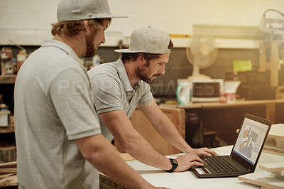 Buy stock photo Cropped shot of two handsome young carpenters checking something on a laptop in their workshop