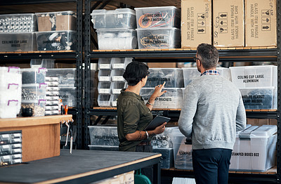 Buy stock photo Shot of a man and woman looking through the shelves together in a workshop