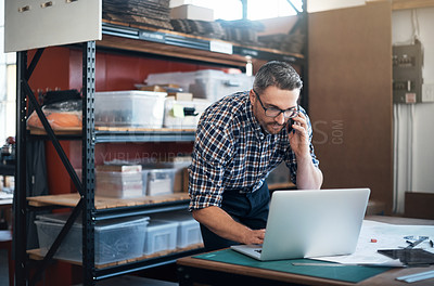 Buy stock photo Shot of a man using a laptop and mobile phone while working on a project in a workshop