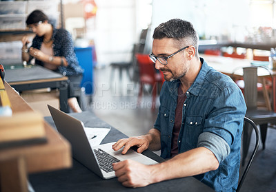 Buy stock photo Shot of a man using a laptop at a table in a workshop