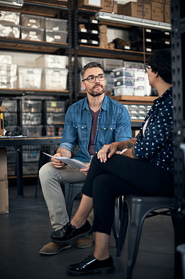 Buy stock photo Shot of a man and woman having a discussion in a workshop