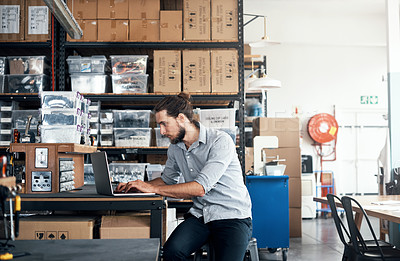 Buy stock photo Shot of a young man using a laptop in a workshop