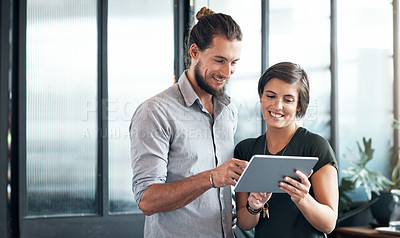 Buy stock photo Shot of two young designers using a digital tablet in an office