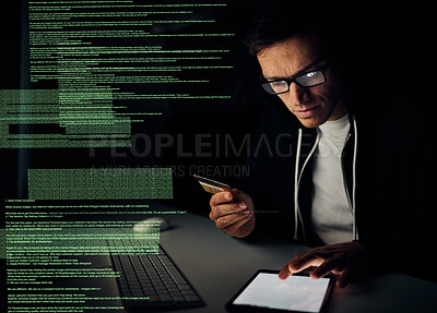 Buy stock photo Cropped shot of a young hacker using a tablet to commit credit card fraud in the dark