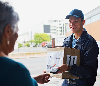 Buy stock photo Cropped shot of a handsome young man delivering a package to a customer and receiving payment with a card