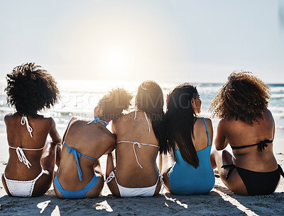 Buy stock photo Rearview shot of a group of young women relaxing together at the beach