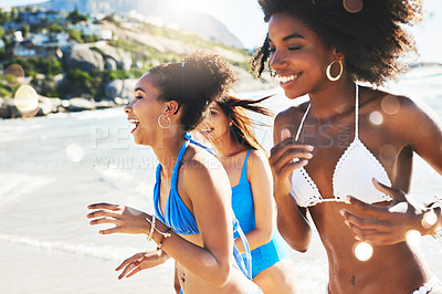Buy stock photo Shot of a group of happy young women having fun together at the beach