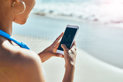 Buy stock photo Cropped shot of a young woman using a mobile phone at the beach