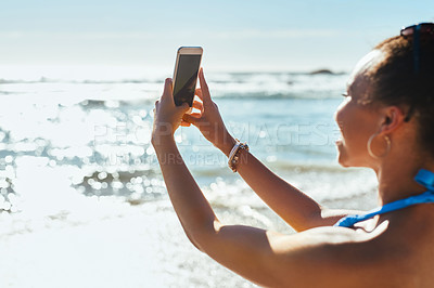 Buy stock photo Shot of a young woman using a mobile phone to take photographs at the beach