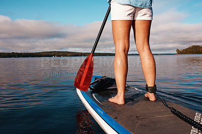 Buy stock photo Cropped shot of an unrecognizable woman paddle boarding on a lake