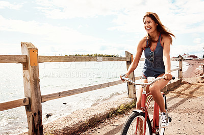 Buy stock photo Shot of a beautiful young woman riding her bicycle on the promenade