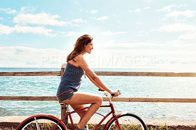 Buy stock photo Cropped shot of a beautiful young woman riding her bicycle on the promenade