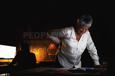 Buy stock photo Shot of a mature businesswoman suffering with back pain while working late in an office