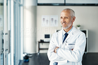 Buy stock photo Shot of a mature doctor standing in a hospital