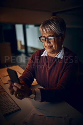 Buy stock photo Shot of a mature businesswoman using a cellphone while working late in an office