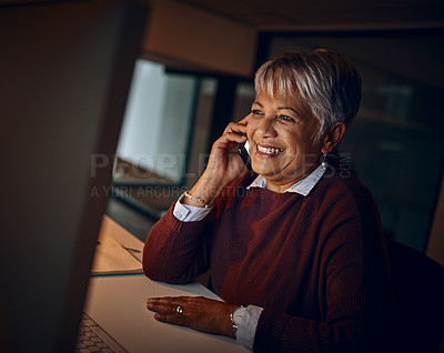 Buy stock photo Shot of a mature businesswoman talking on a cellphone while working late in an office