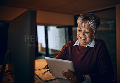 Buy stock photo Shot of a mature businesswoman using a digital tablet while working late in an office