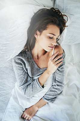Buy stock photo Shot of an attractive young woman lying in bed with her eyes closed at home during the day