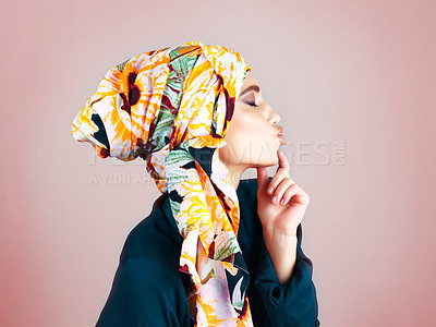 Buy stock photo Studio shot of a confident young woman wearing a colorful head scarf while posing against a pink background