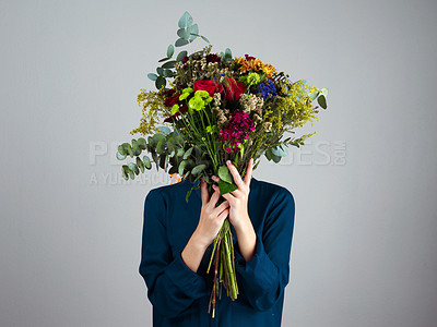 Buy stock photo Studio shot of an unrecognizable woman holding a bouquet of flowers in front of her face while standing against a grey background