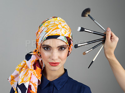 Buy stock photo Studio portrait of a confident young woman wearing a colorful head scarf while looking at different makeup brushes being held in front of her