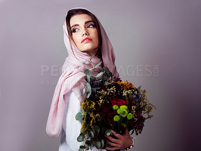 Buy stock photo Studio shot of a confident young woman wearing a colorful head scarf and holding a bouquet of flowers against a grey background
